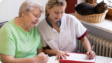 caregiver assisting her patient in writing